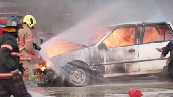 Asijský hasič nosit protipožární oblek s Zachráněným chlapcem v jeho zbraně a hasič bojuje s ohněm na autě během požární cvičení a pomáhá obětem požáru Koncept. Zpomalený pohyb