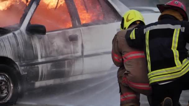 Zadní pohled na asijského hasiče nosit protipožární oblek. Hasič bojující s ohněm na autě při požárním cvičení Dopravní nehoda na požární stanici Koncept. Zpomalený pohyb