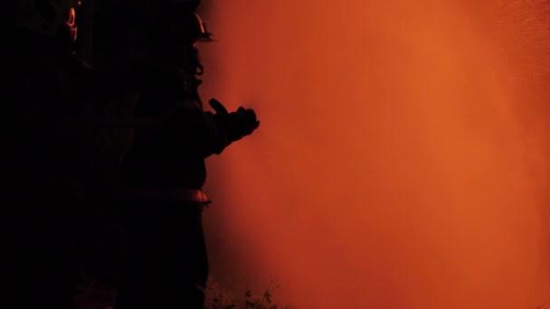 Zadní pohled na asijského hasiče nosit protipožární oblek. Hasiči rozstřikují vodu v noci na požární stanici. Koncepce výcviku požárního cvičení.