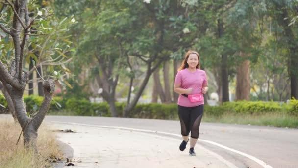 Ázsiai nő kocogás gyakorlat az úton a parkban. Elölnézet Női futás este. Egészség és fitnesz. Lassú mozgás
