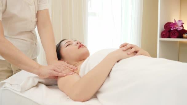 Fiatal ázsiai nő kap spa masszázs kezelés szépségszalonban. Testmasszázs, relaxációs masszázs, spa bőr és testápolás. Lassú mozgás