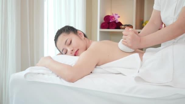 Fiatal ázsiai nő kap spa masszázs Thai Herbal Ball Hot Compress masszázs szépségszalonban. Pihentető masszázs az egészségért. Lassú mozgás