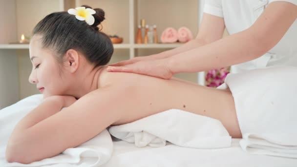 Mladá asijská žena dostává relaxační olejovou masáž v beauty spa salonu. Masáž těla, Masáž pro zdraví. Pomalý pohyb