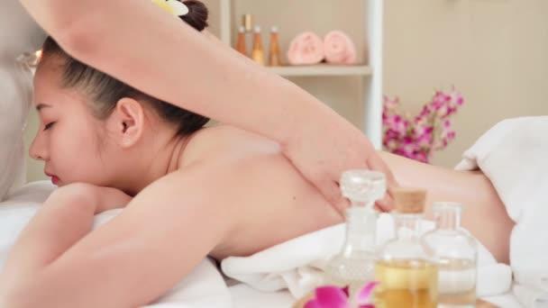 Mladá asijská žena dostává relaxační olejovou masáž v beauty spa salonu. Masáž těla, Masáž pro zdraví. Pomalý pohyb posuvníku Dolly