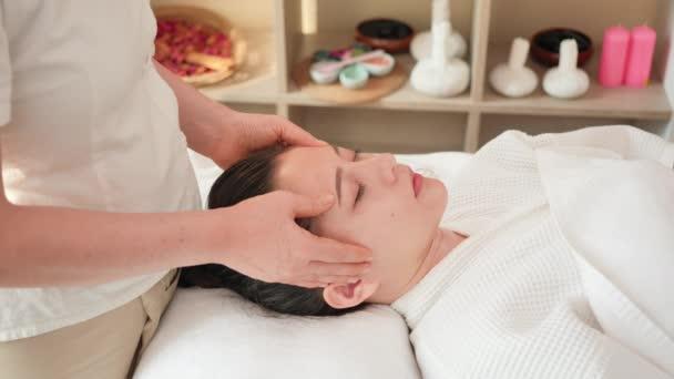 Közelkép Fiatal ázsiai nő kap spa masszázs kezelés szépségszalonban. Arcmasszázs illóolaj bőrápoláshoz, relaxációs masszázshoz, spa bőrápoláshoz és testápoláshoz. Lassú mozgás