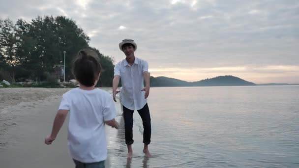 Happy Asian Family On Summer Vacation Boy rushes into hands of father and spinning him around together on the beach In the morning time, sunrise. Holiday and Travel concept. Slow motion