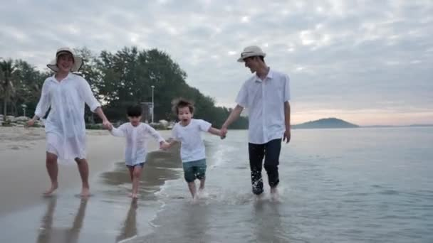Front view Happy Asian Family On Summer Vacation Father, mother, son and daughter running Hand in hand together on the beach In the morning time, sunrise. Holiday and Travel concept. Slow motion