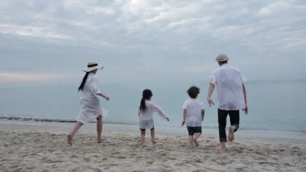 Rear view Happy Asian Family On Summer Vacation Father, mother, son and daughter running into sea together on the beach In the morning time, sunrise. Holiday and Travel concept. Slow motion