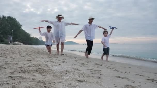 Happy Asian Family On Summer Vacation Father, mother, son and daughter running playing plane flying together on the beach In the morning time, sunrise. Holiday and Travel concept. Slow motion