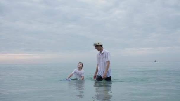 Happy Asian Family On Summer Vacation Father and son playing water sea together on the beach In the morning time, sunrise. Holiday and Travel concept. Slow motion