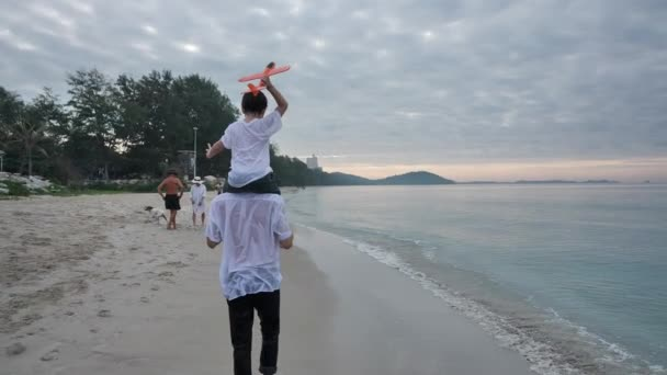 Rear view Happy Asian Family On Summer Vacation Son on fathers shoulders playing plane flying together Walking on the beach In the morning time, sunrise. Holiday and Travel concept. Slow motion