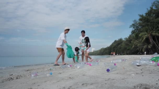 Asian family Father, mother, son and daughter Help each other to collect garbage, Plastic bottles into green plastic bag on the beach. Safe ecology and recycling concept. Slow Motion