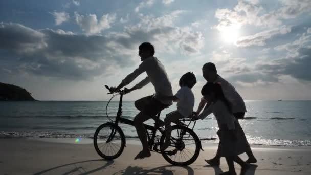 Asijská rodina O letních prázdninách Čtyři lidé Otec, matka, dcera a syn na kolech a procházka Večer západ slunce na pláži Koncept dovolené a cestování. Silueta pomalý pohyb