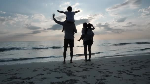 Happy Asian Family On Summer Vacation Children on back fathers and mom Looking at the sky and waved hands on the beach  Background sunset in sea. Relax Holiday and Travel concept. Slow motion