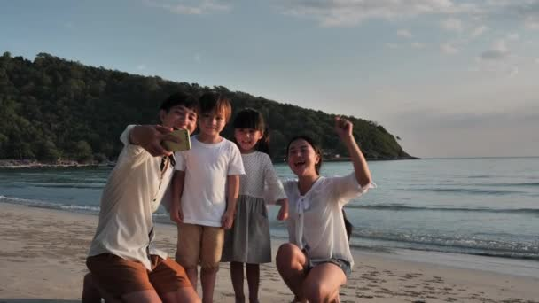 Happy Asian Family On Summer Vacation Father takes family photos with smartphone on the beach. Relax Holiday and Travel concept. Slow motion