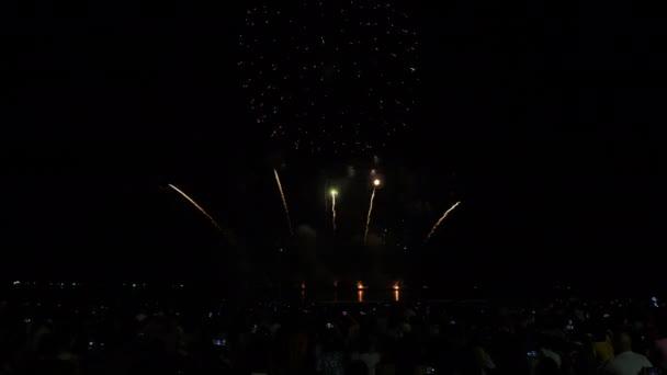 Igazi tűzijáték háttér és az emberek, akik jönnek nézni a strandon Pattaya Nemzetközi Tűzijáték Fesztivál. Szilveszteri tűzijáték ünnep Ázsia Thaiföld