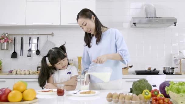 Boldog ázsiai család, hogy a reggelit a konyhában otthon. Az anya, aki tejet önt az üvegbe, reggel adja a lányát. Családi főzés koncepció. Lassú mozgás.