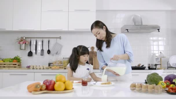 Šťastná asijská rodina dělat snídani v kuchyni doma. Matka nalévá mléko do sklenice a ráno dává dceři. Rodinná koncepce vaření