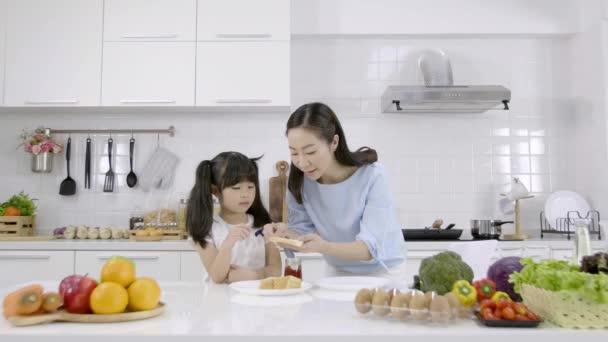 Boldog ázsiai család Anya és lánya segített otthon reggelit készíteni a konyhában. Kenyér lekvárral. Családi főzés koncepciója