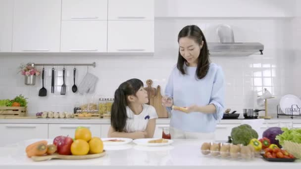 Happy Asian family Mother and daughter helped to make breakfast  in the kitchen at home. Bread with jam. Family Cooking concept