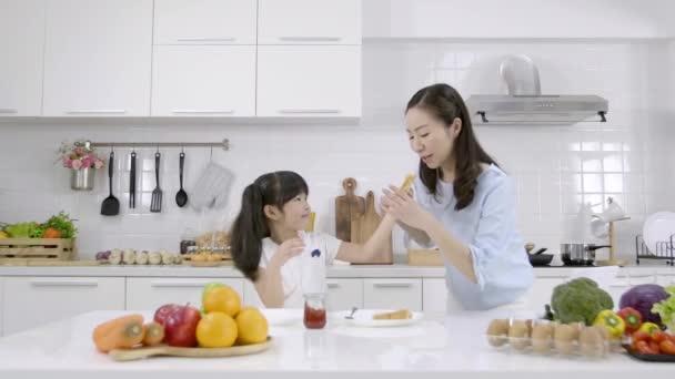 Šťastná asijská rodina Matka a dcera pomohly udělat snídani v kuchyni doma. Chléb s marmeládou. Rodinná koncepce vaření