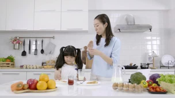 Šťastná asijská rodina Matka a Dívka jsou jíst snídani v kuchyni doma. Chléb se džemem a pijícím mlékem. Koncept zdravé stravy