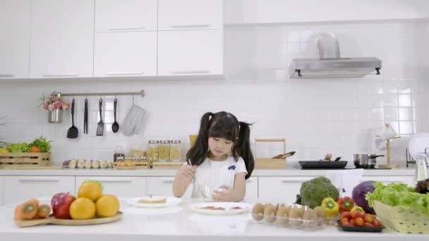 Asijská holčička jí snídani, cereálie s mlékem v kuchyni doma. Zdravý stravovací koncept pro sílu těla. Zpomalený pohyb