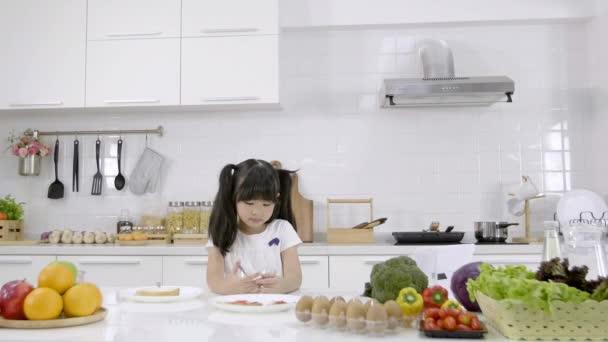 Ázsiai kislány reggelizik, gabonapehely tejjel a konyhában otthon. Egészséges étel koncepció A test erejéért