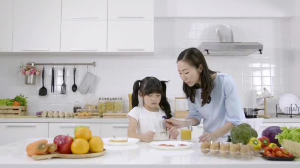 Happy Asian family Mother and Little girl are eating breakfast, cereal  with milk and orange juice in the kitchen at home. Healthy food concept For the strength of the body. Slow motion