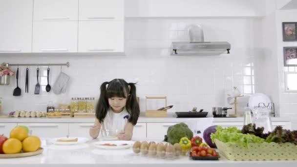 Asijská holčička jí snídani, cereálie s mlékem v kuchyni doma. Zdravá výživa koncepce Pro sílu těla