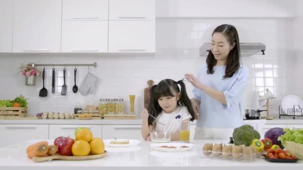 Šťastná asijská rodina Matka a Dívka jsou jíst snídani, cereálie s mlékem a pomerančový džus v kuchyni doma. Zdravá výživa koncepce Pro sílu těla
