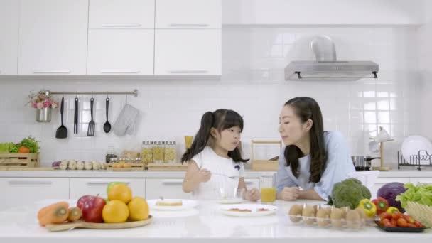 Šťastná asijská rodina Matka a Dívka jsou jíst snídani, cereálie s mlékem a pomerančový džus v kuchyni doma. Zdravý stravovací koncept pro sílu těla. Zpomalený pohyb