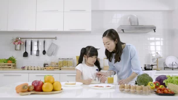 Happy Asian family Mother and Little girl are eating breakfast, cereal  with milk and orange juice in the kitchen at home. Healthy food concept For the strength of the body