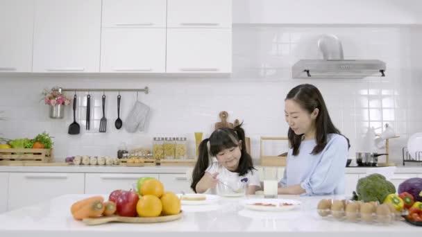 Boldog ázsiai család Anya megjelenés Kislány eszik reggeli, gabonapehely tejjel a konyhában otthon. Egészséges étel koncepció A test erejéért