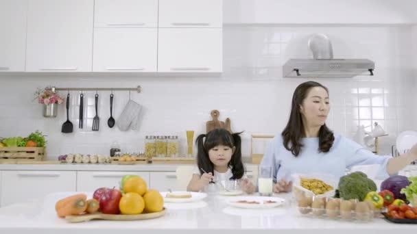 Šťastná asijská rodina Matka a Dívka jsou jíst snídani v kuchyni doma. Rodinná koncepce vaření