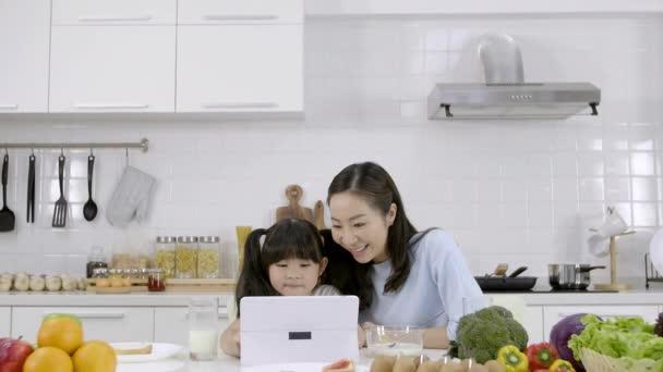 Šťastná asijská rodina Matka a Dívka jsou jíst snídani, cereálie s mlékem, Chléb s džemem a vidět digitální tablet v kuchyni doma. Zdravé jídlo a ranní aktivity