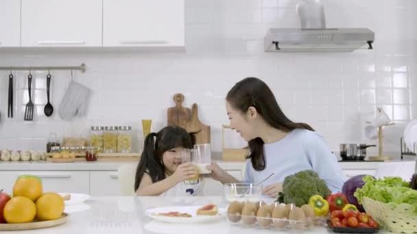 Šťastná asijská rodina Matka a Dívka jsou jíst snídani, pít mléko a pít pomerančový džus v kuchyni doma. Zdravá výživa koncepce Pro sílu těla