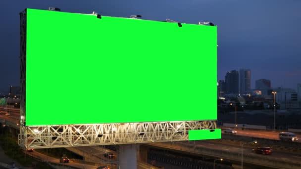 Zelená obrazovka reklamního billboardu na dálnici za soumraku s městským pozadím v Bangkoku, Thajsko.