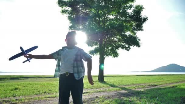 Šťastné asijské dítě chlapec házejí hrát letadlo simulovat v přírodě, stromy a travnaté porosty venku, který má sluneční světlo ve večerních hodinách. Šťastná dovolená Pomalý pohyb