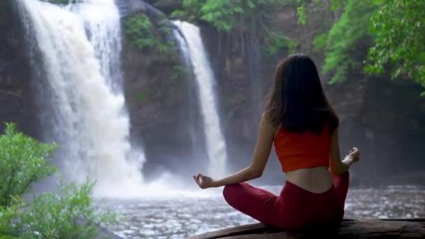 Rückansicht Asiatin, die am Wasserfall Yoga praktiziert oder macht, Lotus posiert bei einer Meditationssitzung. Schöne Landschaft, Natürlicher Hintergrund, Thailand.