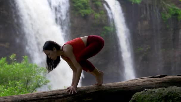 Asian woman practicing or doing yoga at the waterfall. Beautiful Landscape, Natural background, Thailand.  Female professional yoga
