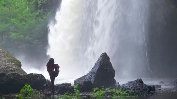 Asijka cvičí nebo cvičí jógu u vodopádu. Krásná krajina, přírodní zázemí, Thajsko. Ženská profesionální jóga