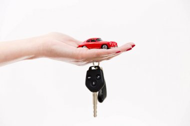 Car purchase concept. Toy car on woman's palm, car keys on finge