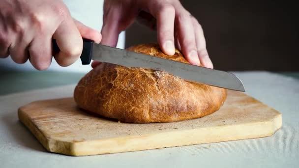 Chef baker cuts fresh italian bread