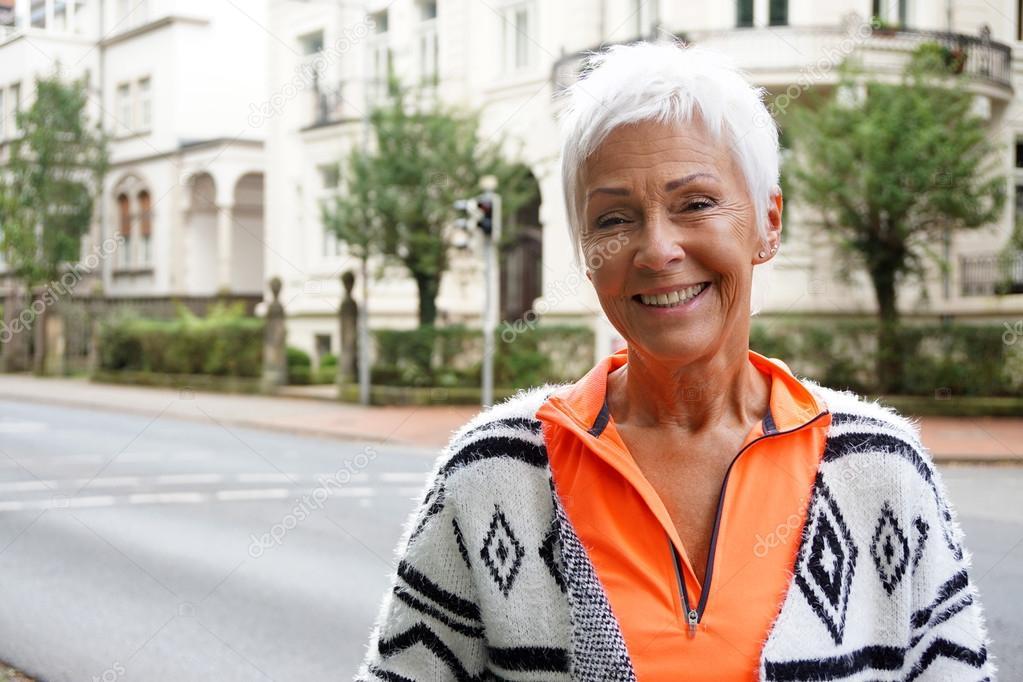 Donna matura sorridente felice con look sportivo alla moda fuori sulla  strada — Foto di buecax 15328d3afd47