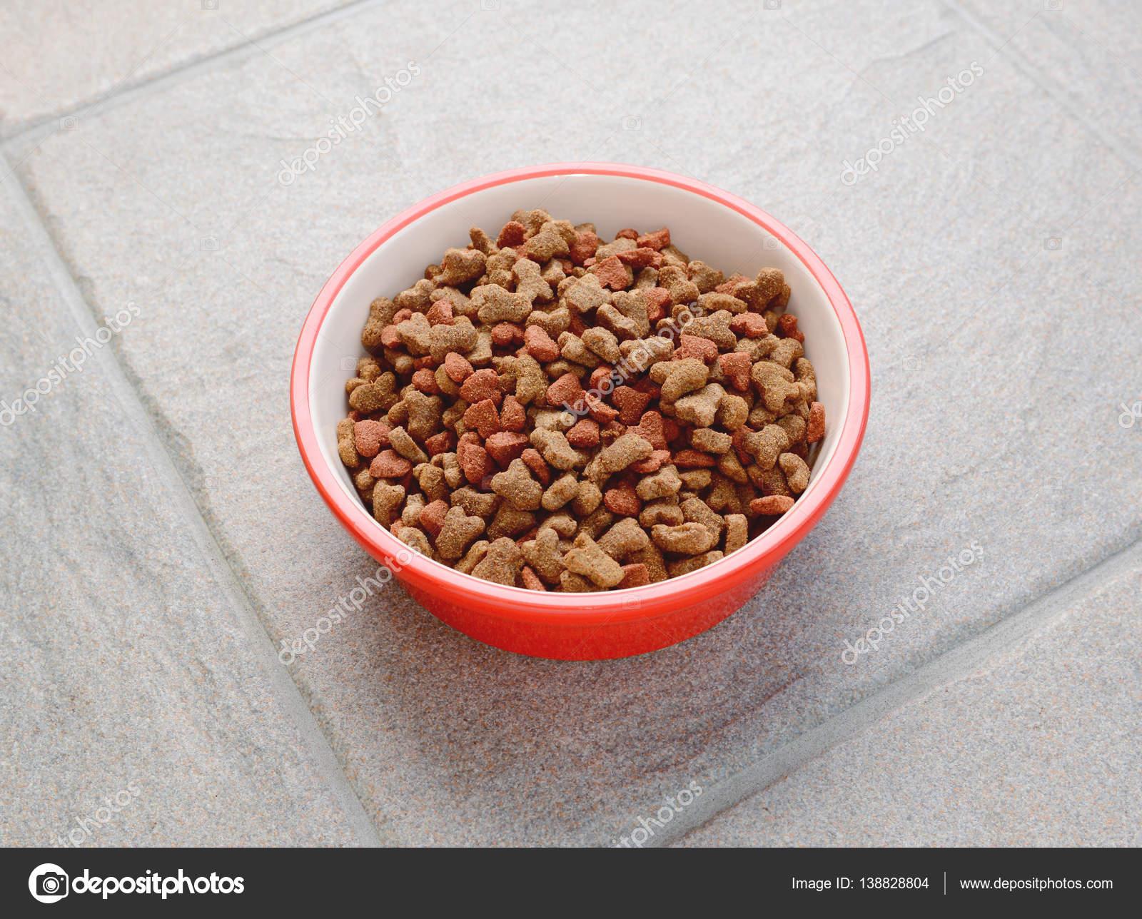Ciotola rossa di cibo per gatti secco su grigio piastrella u2014 foto
