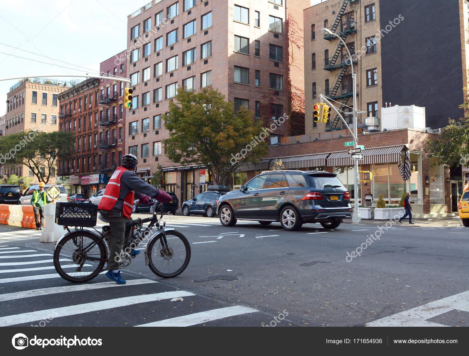 Ciclista de entrega esperando en rojo en la cocina del infierno ...