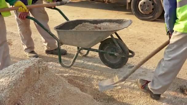 UHD staveniště, dělníci zatížení pískem manuálně pro concrite přípravu. Sony 4k snímku