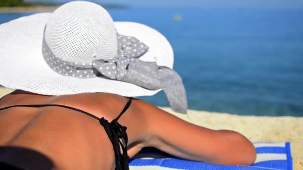 nő a kalap napozásra a strandon nyaralás alatt