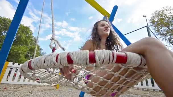 View of young girl in swimsuit having fun on beach swing